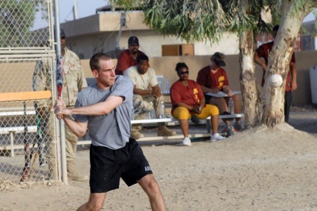 "BAGHDAD - Sgt. Daniel Ehardt, an operations sergeant serving with Headquarters and Headquarters Company, 56th Infantry Brigade Combat Team, keeps his eyes on the ball as he prepares to swing away during the championship game of a Morale Welfare and Recreation center sponsored softball tournament on June 11 at Camp Victory, Iraq. Ehardt, from Granbury, Texas stated after the game, ""two in a row, that's what I call a VBC dynasty."""