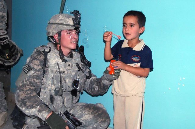 "BAGHDAD - Spc. John Wayne Ringer, from Waynesburg, Pa, of Company B, 2nd Battalion, 112th Infantry Regiment ""Paxton Rangers,"" 2nd Heavy Brigade Combat Team, 1st Infantry Division, teaches a child to blow bubbles at a youth center in the Abu Ghraib district west of Baghdad during a supply drop, June 11. The Soldiers visited the center to better the partnership between the Soldiers and the population of Abu Ghraib."