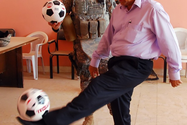 """BAGHDAD - Director Hansen, of the Abu Ghraib Youth Center, dribbles one of the 50 soccer balls presented as a gift by Capt. Jason Hoffman, from York, Pa., with Company B, 2nd Battalion, 112th Infantry Regiment """"Paxton Rangers,"""" 2nd Heavy Brigade Combat Team, 1st Infantry Division, June 11."""