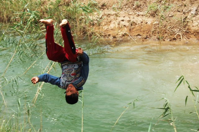 TAJI, Iraq - A child somersaults into a canal June 12 in a village just north of Baghdad. While on patrol in the village, Soldiers from the 1st Battalion, 112th Infantry Regiment, 56th Stryker Brigade Combat Team watched as the boy jumped into the canal, taking a swim in order to beat the summer heat. The canal acts as the water source for a new water treatment plant in Asaf, Iraq near Taji.  The new facility provides clean water to over 80 nearby homes.
