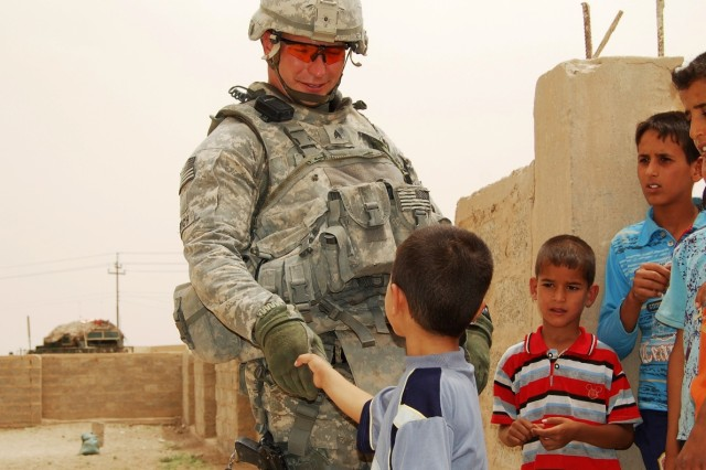TAJI, Iraq -Sgt William Emerich of Hermitage, Pa., a Soldier with Company A, 1st Battalion, 112th Infantry Regiment, 56th Stryker Brigade Combat Team, Multi-National Division - Baghdad, greets a small child outside Nahalla Elementary School, north of Baghdad, June 12. Emerich and Soldiers of his unit were in the area to inspect the school and a nearby water treatment facility.