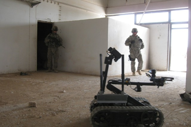 "BAGHDAD-Sgt. 1st Class Bruce Mcrae (right) of San Antonio, Texas and Staff Sgt. James Bohanon (left) of Belleville, Ill., supervise an explosive ordinance disposal robot as it is controlled remotely by Iraqi Security Forces Soldiers in training.  Mcrae and Bohanon are assigned to the 1st Brigade Special Troops Battalion, 1st ""Ironhorse"" Brigade Combat Team, 1st Cavalry Division."