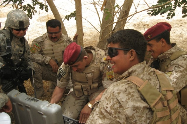 """BAGHDAD-Lt. Col. Maria Zumwalt (far left), a native of Puerto Rico and commander of the 1st Brigade Special Troops Battalion, 1st """"Ironhorse"""" Brigade Combat Team, 1st Cavalry Division, observes and discusses the effectiveness of the explosives ordnance joint training session with Lt. Mohammed Arif (center) and his Soldiers.  The Iraqi platoon is assigned to the Explosives Ordnance Detachment Company, Engineer Regiment, of the 11th Iraqi Army Division and partnered with Zumwalt's Soldiers."""