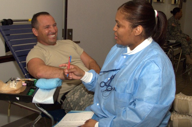 Conlela Isom, a phlebotomist with the Robertson Blood Center double-checks the paperwork of Sgt. Major Lawrence McCullar before collecting his donation June 18, 2009 at Fort Hood.""