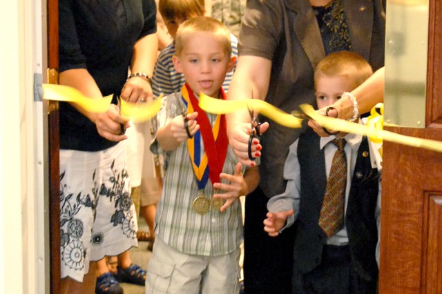 Cameron Jessen, 5, cuts the ribbon on the conference room at Aberdeen Proving Ground dedicated to his father who was killed in Iraq.