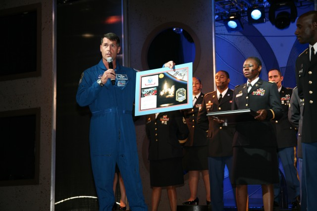 Army astronaut Lt. Col. Shane Kimbrough representing the Space and Missile Defense Command/Army Forces Strategic Command presents a montage to the Soldier Show participants at the end of the 3 p.m. show June 17. The montage included photographs and a crew patch as well as a small flag which was flown in space during Kimbrough's mission to the International Space Station in November as part of STS-126.