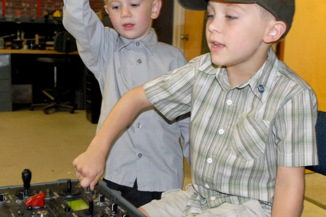 Cameron Jessen works the controls of an EOD robot while his cousin, Michael Miller, directs the movement.