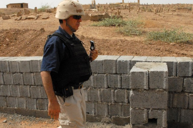 Abbas Ali, from Vancouver, Canada and a civil engineer with the Provincial Reconstruction Team in Kirkuk, Iraq, checks the construction status of a retaining wall to protect a cemetery from a construction project to build roads connecting facilities in the Iraqi village of Kardaara in Kirkuk province June 11.