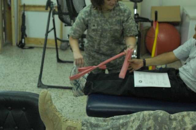 """TAJI, Iraq - Sgt. Angela Horst of Silver Springs, Md., a physical therapy technician with Company C """"Charlie Med,"""" 328th Brigade Support Battalion, places an elastic band on the foot of a patient June 13 at Camp Taji, north of Baghdad. In the foreground, another patient is having his knee examined by electrodes."""