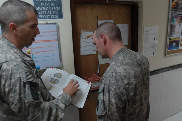 """TAJI, Iraq - Lt. Col. Kevin Koehler (left) of Pontotoc Miss., an Arkansas National Guard  physician on a 90-day rotation to Camp Taji, Iraq explains the structure of the human knee  to Sgt. Christopher Walker of York, Pa., a healthcare specialist, with Company C. """"Charlie Med,"""" 328th Brigade Support Battalion, 56th Stryker Brigade, June 13 at Camp Taji, north of Baghdad. Walker had just finished a consultation with a patient who complained of knee pain. Koehler practices in Tupelo, Miss."""