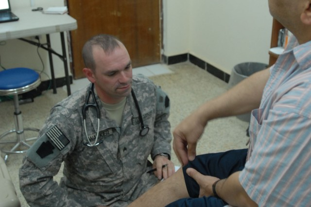 """TAJI, Iraq - Sgt. Christopher Walker of York, Pa., a healthcare specialist, with Company C """"Charlie Med,"""" 328th Brigade Support Battalion, 56th Stryker Brigade, listens June 13 at Camp Taji, Iraq, north of Baghdad, as a civilian patient talks about knee pain that has limited his mobility."""