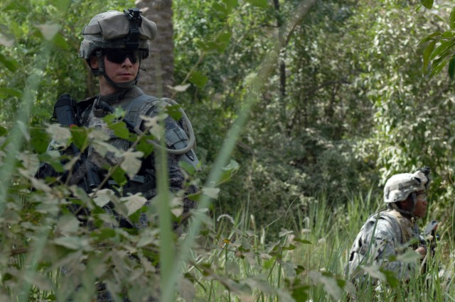 "BAGHDAD - North Carolina National Guardsmen Spc. James Britt (left) of Pautego, N.C., and Spc. Juan Gonzalez (right) of Asheville, N.C., take a break while searching for weapons caches in a palm grove in Doura, here, June 13. Both Soldiers are infantrymen assigned to Company A, 252nd Combined Arms Battalion, 30th Heavy Brigade Combat Team. ""It helps Iraq because it might give them a chance to do something with their lives and not live in fear,"" Gonzalez said. ""Freedom is a big thing, you know."""
