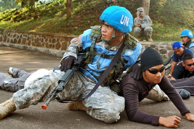 Staff Sgt. Ray Jay Aromin, an infantryman assigned to the 1st Battalion, 294th infantry Regiment, Guam  National Guard, shields a role player from scenario-driven gunshots during a peacekeeping scenario as part of Exercise Garuda Shield 09, at the Tentara Nasional Indonesia-Angkatan Darat, or Indonesian Army, Infantry Training Center in Bandung Indonesia, June 22. Garuda Shield is a two week exercise brings together Soldiers and Marines from nine Nations to train on the UN mandated ground-level tasks.  GS09 is the latest in a continuing series of exercises designed to promote regional peace and security.  Training will focus on peace Support Operations and Global Peace Operation Initiative Certification, a Command Post Exercise, a Field Training exercise and Humanitarian and Civic Assistance Projects.