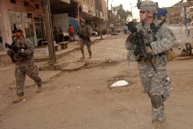 BAGHDAD –Soldiers of B Company, 252nd Combined Arms Battalion, 30th Heavy Brigade Combat Team patrol through a market place in the Saydiyah district of southern Baghdad, June 9.  During a patrol, Soldiers must balance security with politeness while approaching Iraqi civilians in an attempt to gain information about the area.