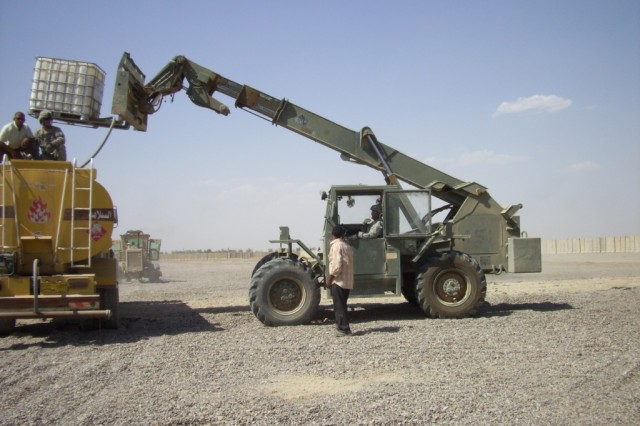 "BAGHDAD - Sgt. Augustine Deluna, heavy equipment operator, 277th Engineer Company, 46th Engineer Combat Battalion (Heavy), 225th Engineer Brigade, a native of San Antonio, lifts 250 gallons of a mixture called ""rhino snot"" which is used to keep dust and small sand particles down on the helicopter landing zone they were constructing June 13 at Joint Security Station Istiqlaal.  Soldiers sit on top of a water distributor to make sure the mixture of ""rhino snot"" and water is at a proper level."