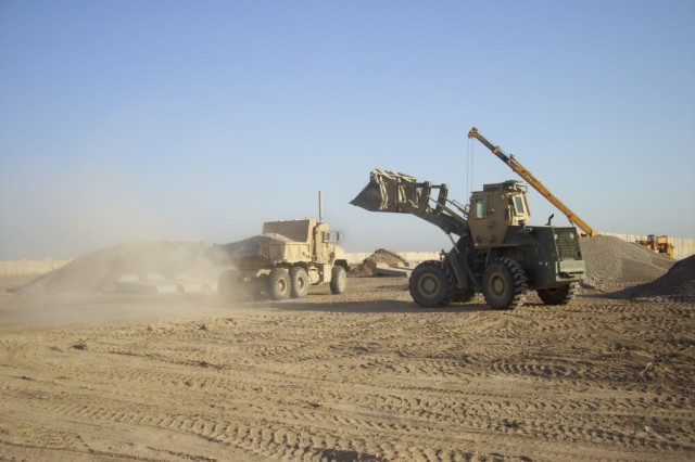 BAGHDAD - Spc. Andrew Leach, heavy equipment operator, 277th Engineer Company, 46th Engineer Combat Battalion (Heavy), 225th Engineer Brigade,, a native of San Antonio, uses a loader to fill a dump truck with the aggregate to be spread on the access road for local Iraqi Police stations June 13 near Joint Security Station Istiqlaal.  The heavy equipment and Soldiers working attracted attention from the local children who would come out to watch the work being done.