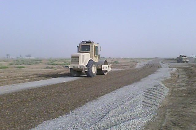BAGHDAD - A heavy equipment operator from the 277th Engineer Company, 46th Engineer Combat Battalion (Heavy), 225th Engineer Brigade, uses a roller to compact the access road outside Joint Security Station Istiqlaal June 13.  While working on the access road the Soldiers had many spectators, made up mostly of local Iraqi children who watched the engineers completing their work.