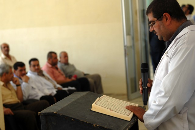 BAGHDAD - An Iraqi doctor reads a prayer from the Quran to begin the re-opening ceremony of the al-Hamza Center for the Disabled in Yarmouk, here, June 15. The building renovation was funded by Coalition forces and took an Iraqi contractor about three months to complete.