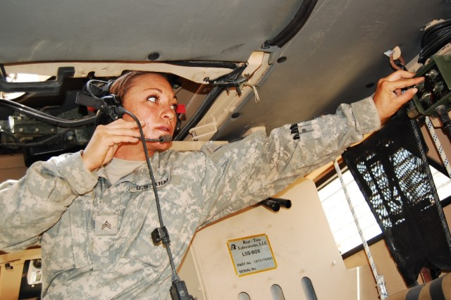 BAGHDAD - Sgt. Frankie Hibberd, a signal specialist with Company D, 230th Brigade Support Battalion, 30th Heavy Brigade Combat Team, checks the frequency and volume of radio headsets before an early morning convoy, June 11. The Charleston, W. Va. native said she nearly didn't deploy after doctors found she had pre-cancerous cervical cells.