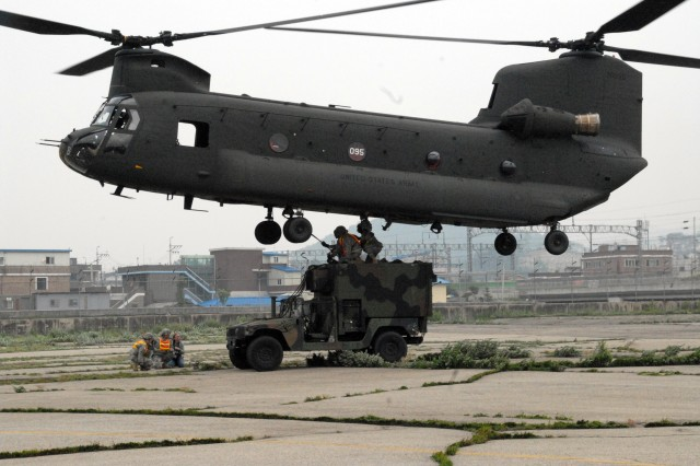 (from left to right) Pfc. Joseph Thames, C Company 304th Signal Battalion cable system installer, Pfc. Leonard Ahmai, C Company 304th Signal Battalion multichannel transmission systems operator and Staff Sgt. James Green, non commissioned officer in charge of sling load operations, attach cables from their Humvee to the CH-47 Chinook flying above them during a Sling Load Operation June 16 at the Camp Mobile Airfield. The Sling Load involved C Company 304th Signal Battalion hooking up two of their Humvee's to the incoming CH-47 Chinooks while in the air; the mission was the first time for both Thames and Ahmai.