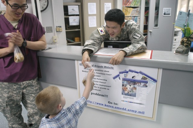 "(Left) Damien Floyd (center) hands cookies to Sgt. Joonghyo Lee, 618th Dental Company senior KATUSA, at USAG-Red Cloud Troop Medical Clinic. USAG-Red Cloud Pear Blossom Cottage baked cookies and delvered them to soliders in the garrison June 17 in celabration of 234th Army birthday. - U.S. Army photo by Pfc. Kim, Tae Hoon. (Right) Lt. Col. Alfred Francis cuts the Army's birthday cake with soon to be Pvt. Joshoa Hammond during the Army birthday celebration given in Camp Stanley's Pear Blossom Cottage June 16. Francis thanked all the volunteers working in the Cottage for all they do for Soldiers and their Famlies and gave certificates of appreciation. ""This celebration is about all of you who volunteer to make life better for the Soldiers and their Families,"" Francis said. ""Although these certificates look small, they mean a lot. Every time I look around I see all of you volunteering your time here at the Cottage. You service is not going unrecognized."" Preparations for the celebration took volunteers 16 hours, which included baking the birthday cake and preparing food representing cuisine from different parts of Asia. - U.S. Army photo by Jim Cunningham"