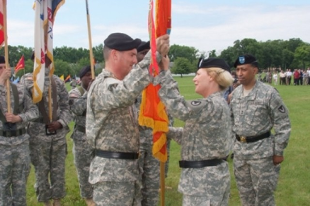 General Ann E. Dunwoody, commanding general, U.S. Army Materiel Command, passes the CECOM colors to Maj. Gen. Randolph P. Strong as Maj. Gen. Dennis L. Via (right), Command Sgt. Maj. Tyrone Johnson (partially obscured) and the color guard look on.