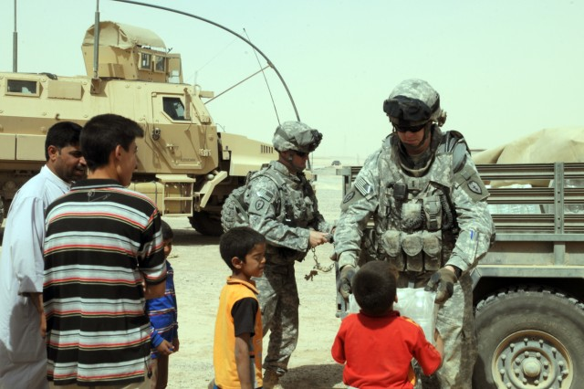 "CONTINGENCY OPERATING BASE SPEICHER, TIKRIT, Iraq - Capt. Jason Honeycutt (left) and 1LT Gavin Mohrman (right) hand humanitarian supplies to children from a small village in Sharqat district during a community outreach, June 2. Iraqi Police and ""Wolfhound"" Soldiers of Co. B, 2nd Battalion, 27th Infantry Regiment, 3rd Infantry Brigade Combat Team, 25th Infantry Division delivered humanitarian supplies. (U.S. Army photo by Spc. Jazz Burney, 3rd Infantry Brigade Combat Team Public Affairs, 25th Infantry Division)"