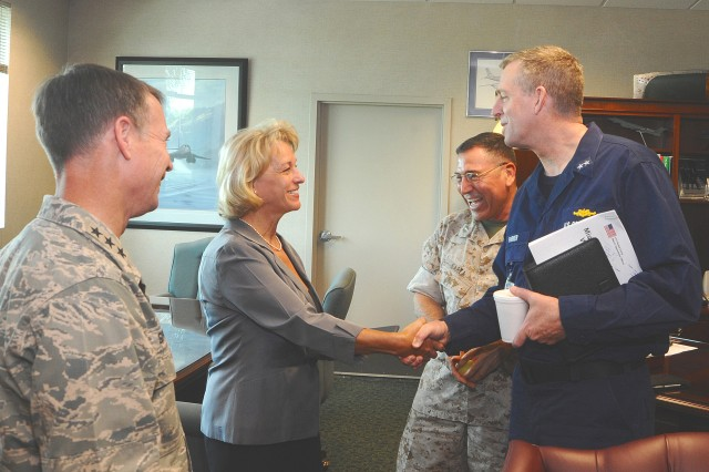 "Marianne Winch receives a coin from RADM Robert Parker, U.S. Southern Command Chief of Security and Intelligence, as Lt. Gen. Glenn F. Spears (left) SOUTHCOM Deputy Military Commander and Brig. Gen. David Garza (right), SOUTHCOM Chief of Staff look on.  Winch was honored in Spears' office for the exceptional quality of service she exhibited as a housing manager for SOUTHCOM's senior staff.  ""Marianne represents the SOUTHCOM Gold Standard in her approach to service to the customer, and we are very proud that she is on the SOUTHCOM Team,"" Garza said."