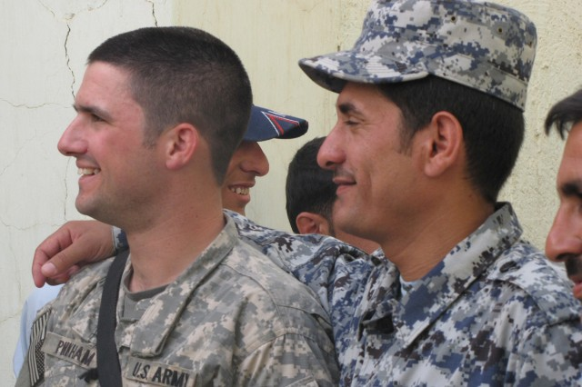 1st Lt. Steve Pinkham and Officer Faras Abbas Shakour share a smile after a barbecue at the Amerli Police Station, June 16.  Pinkham's platoon has been conducting warm basing operations with the Amerli police for several weeks, and the two groups celebrated their successful partnership with a small gathering at the station.