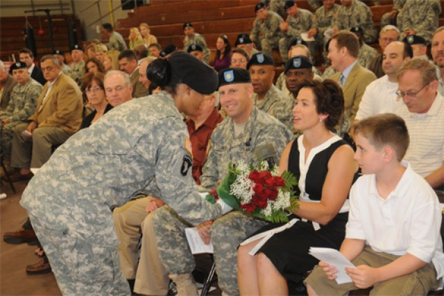Karla New, wife of Lt. Col. Corey A. New, incoming commander, 53rd Transportation Battalion, receives a bouquet of roses flanked by her husband and son, Camden.