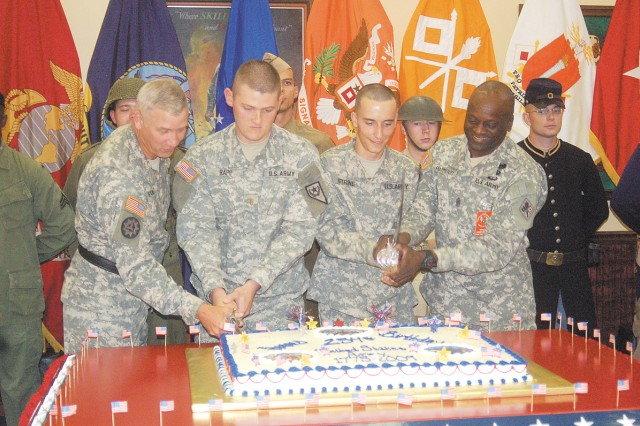 FORT GORDON, Ga.--(Left to right) Brig. Gen. Jeffrey Foley, U.S. Army Signal Center and Fort Gordon commanding general, 2nd Lt. Jason Rapp, youngest officer, Pvt. Jacob Strine, youngest enlisted Soldier and Command Sgt. Maj. Vernon Praymous, Regimental Noncommissioned Officer Academy commandant, cut the official Fort Gordon 234th Army birthday cake June 12 at Conrad Hall.