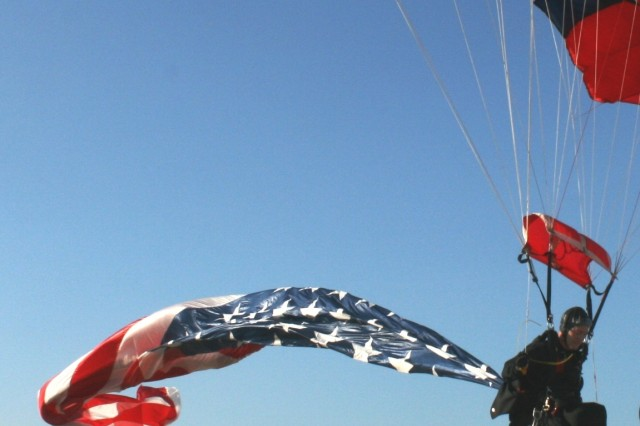 Sgt. Richard Sloan, 82nd ABN 'All American' Freefall Team, Fort Bragg, NC jumps over the heads of members of the Illinois Army National Guard, waiting to catch the flag while he lands onto the North Avenue Beach on 23 June, 2009, in Chicago, IL.  Sloan jumped in a 750 Square Foot (40 Feet Long by 20 Feet Wide) American Flag, for the first time in his team's history, at a show demonstration in front of over 10,000 spectators.  Sloan was in the Windy City for the Chicago 2016 Olympic Committee Celebration.