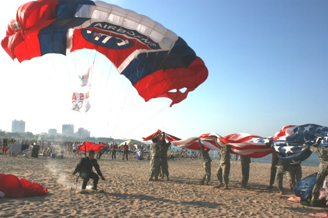 """Sgt. Chris Clark, Team Leader for the 82nd Airborne Division 'All American' Freefall Team, Fort Bragg, NC, kicks up sand as he brings in the Chicago 2016 Olympic Bid and USA Olympic Rings Flag, for their 'Olympic Day' celebration at North Avenue Beach.  Clark pleased the """"I support the Olympic Bid"""" crowd of over 10,000, on Tuesday, 23 June, 2009. To the right are members of the Illinois Army National Guard, protecting the American Flag that teammate Sgt. Sloan jumped in."""
