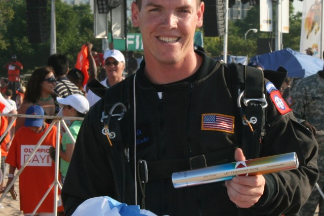 Staff Sgt. Jimmy Hackett, 82nd Airborne Division 'All American' Freefall Team, Fort Bragg, NC displays the Chicago 2016 Olympic Baton after executing a jump with it attached to his flight suit, for the 10,000 spectators at North Avenue Beach on 23 June, 2009. In the background of the shot is his host, Mr. Joe Ahern, the Public Relations Director for the 2016 Olympics.  Afterwards, the team presented the baton officially to the 2016 Olympic Chairman, Pat Ryan and Bob Berland, 1984 USA Olympic Silver Medalist in Judo.