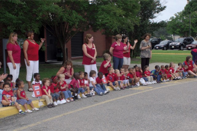 CDC staff, parents and toddlers line the parade route during the festivities.