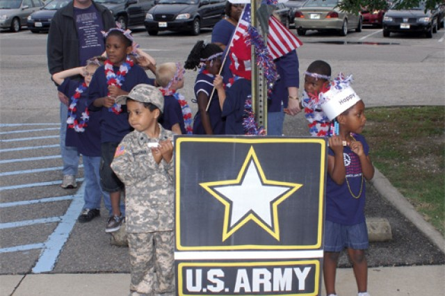 Javyn Eisenhower, left, and Nylah Simpson, both with the CDC's 1st Step Program, carry a U.S. Army banner during the parade.
