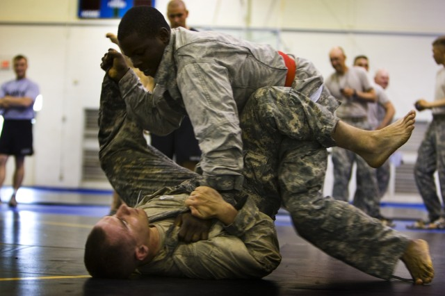 Battling for hand control at 1-64 Armor's grappling and combatives competition, Pfc. Rasheem Ruffin (top) and Spc Phil Mancini (bottom) 1-64 AR, 2nd HBCT, 3rd ID,  duke it in Marne style on the mat during Rogue Rumble at Fort Stewart's Caro