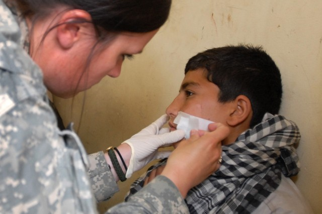 Spc. Danielle Lafoille, a combat medic from Manistique, Mich., places a bandage on an Afghan boy at Forward Operating Base Blessing, April 7. The boy is one of the more than 4,000 Afghans treated by 1st Battalion, 26th Infantry Regiment, 1st Infantry Division, Soldiers at FOB Blessing's aid station since July of last year.