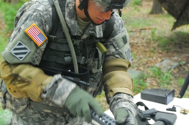 Specialist Joshua Heffelbower, B Co., 4-3 BSTB, reassembles an M249 Squad Automatic Weapon, during his battalionAca,!a,,cs Sentinel Stakes challenge, June 16.