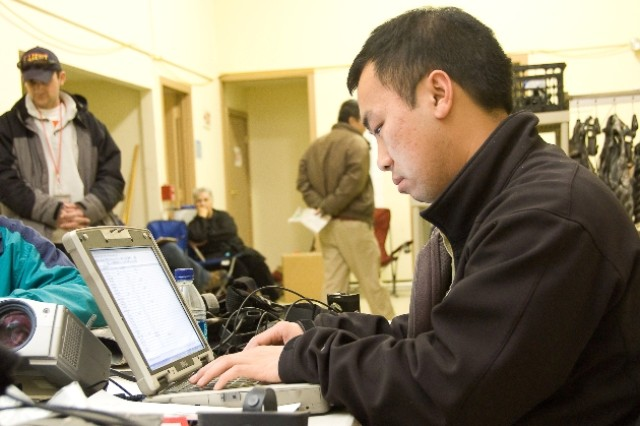 Dinh Nguyen of the Software Engineering Center at Fort Monmouth, N.J., sets up the plans for the day's test of the Rifleman radio.