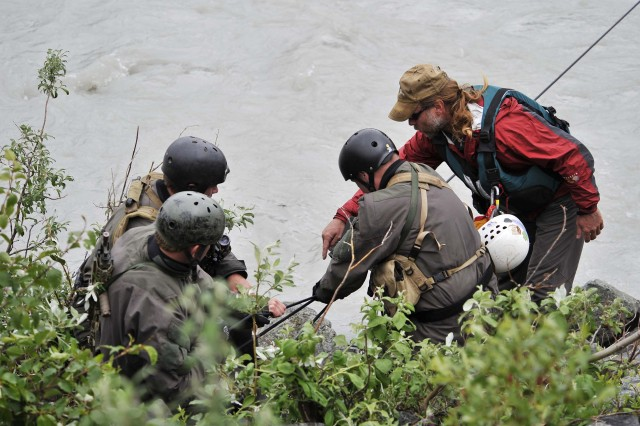 Steven Decker of the Northern Warfare Training Center teaches a group of Navy SEALs rope techniques during a river-crossing exercise at Phelan Creek during Northern Edge 2009, June 17.