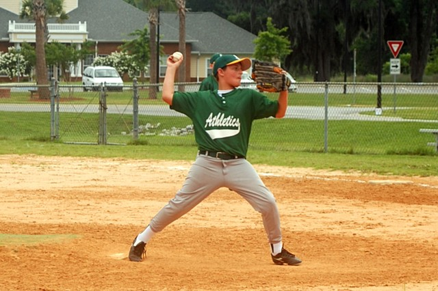 Josh Musiol, son of Lt. Col. Mike Musiol, commander of 1/3 Combat Avn. Regt., throws a pitch during the Hunter Athletics' game against the Island YMCA, June 13, at Hunter Army Airfield.
