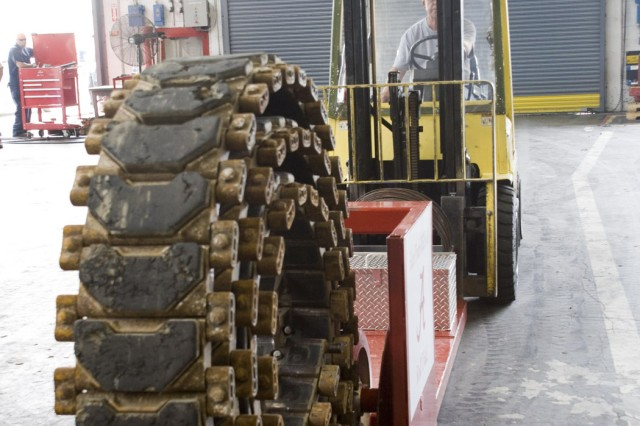 Before using the track roller, workers would have to use the mast of the forklift to reach this point in the roll-up process. The track roller being used in the photo helps with efficiency and safety in the Paladin and FAASV production process at Anniston Army Depot, Ala.