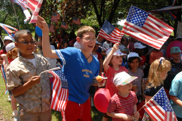 """Children from School-Age Services, including Ricky Glover, Phillip Conners and his brother Ethan Conners, sing the """"Army Song"""" for staff assembled in front of Fort Leavenworth, Kan., Garrison Headquarters to celebrate the Army birthday June 18."""