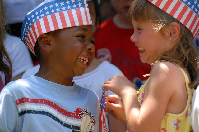 """Jonathon Lucas and Madison Gill, kindergartners from the Child Development Center, wave flags as children from the CDC and School-Age Services assemble after parading from the Patch building to the Fort Leavenworth, Kan., Garrison Headquarters June 18. Eight-year-old Zoe Dunn sang the national anthem, the middle school/teen program signed """"America the Beautiful,"""" and all the children sang the """"Army Song"""" to celebrate the Army's 234th birthday."""