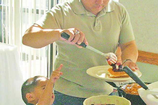 Sgt. Kevin Rodriguez, A Co., 701st BSB, 4th IBCT, scoops raspberries onto his son's waffle during the Father's Day Brunch June 21 at Riley's Conference Center. Along with breakfast foods barbeque was served during the barbeque themed brunch. Post/Born
