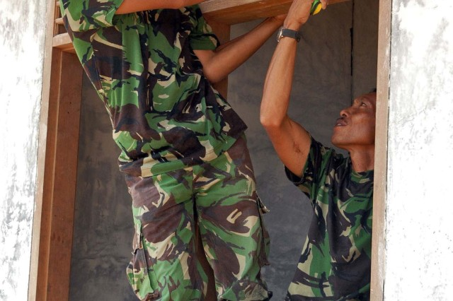 Two engineers from the Tentara Nasional Indonesia-Ankatan Darat, or Indonesian Army, work on framing a window at the Baby Care Clinic, approximately 20 minutes outside Bandung, Indonesia June 21. This project is one of three Humanitarian and Civic Assistance projects part of Exercise Garuda Shield 09. The two-week exercise brings together Soldiers and Marines from nine Nations to train on the UN mandated ground-level tasks.  GS09 is the latest in a continuing series of exercises designed to promote regional peace and security.  Training will focus on peace Support Operations and Global Peace Operation Initiative Certification, a Command Post Exercise, a Field Training exercise and Humanitarian and Civic Assistance Projects.