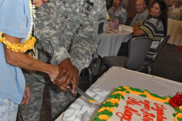 FORT SHAFTER, Hawaii-Col. Bruce Crawford, commander, 516th Signal Brigade,  helps Nancy Kanbara cut her retirement cake during a luncheon honoring her 52 years of federal service.