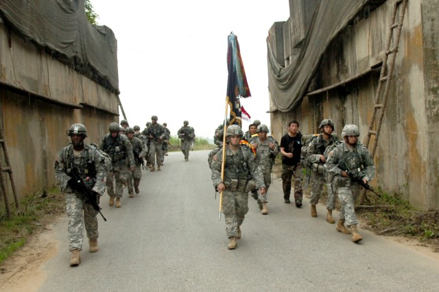 The command team of 2nd Battalion, 9th Infantry Regiment, march through a 'rock drop' June 25 outside Warrior Base, South Korea. The Battalion was conducting its bi-annual 'Manchu Mile', a 25-mile tactical roadmarch with full combat