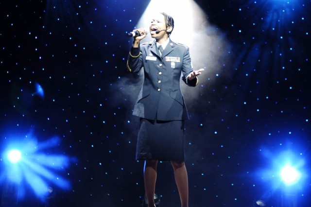 """""""Lights, Camera, Action"""" was the theme of the 2009 Soldier Show and Sgt. Dawn Florence performs a solo while bathed in lights. Florence's singing was part of the 90-minute show performed for the Fort McPherson and Fort Gillem communities June 21 at the Clayton County Schools' Performing Arts Center in Jonesboro. """""""